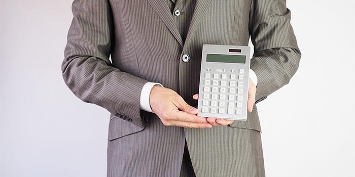 電卓を持つスーツの男性