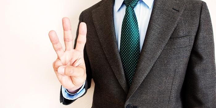 3本指を立てるビジネスマン